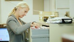 De bedrijfsvrouw neemt een omslag met documenten van een lade in retro stijl stock videobeelden