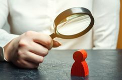 De bedrijfsvrouw onderzoekt een rood man cijfer door een vergrootglas Analyse van de persoonlijke kwaliteiten van de werknemer royalty-vrije stock foto