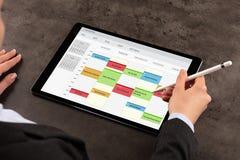 De bedrijfsvrouw plant haar programma over tablet royalty-vrije stock foto