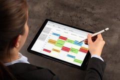 De bedrijfsvrouw plant haar programma over tablet stock afbeeldingen