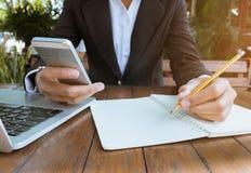 De bedrijfsvrouw schrijft bij notitieboekje en de telefoon van de gebruikscel werken openlucht in de uitstekende toon van de koff Royalty-vrije Stock Fotografie