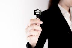 De bedrijfsvrouw toont de zwarte sleutel op witte achtergrond Sleutel tot succesconcept Stock Fotografie