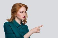 De bedrijfsvrouw toont iets geïsoleerd op witte achtergrond stock fotografie