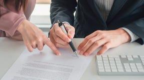 De bedrijfsvrouw verzendt document naar zakenman voor handtekening op zijn bureau stock afbeeldingen