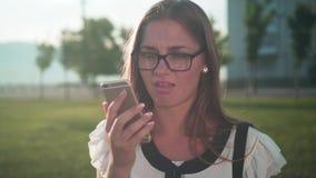 De bedrijfsvrouw in witte overhemd en glazen spreekt telefonisch, is het meisje onverschillig en ontmoedigend aan de gesprekspart stock footage