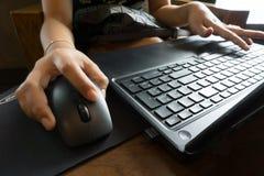 De bedrijfsvrouwen overhandigen het werken met laptop en muis Stock Foto's