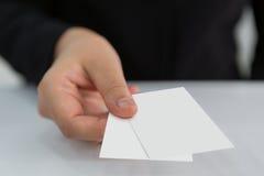 De bedrijfsvrouwen overhandigen holding leeg document adreskaartje stock foto