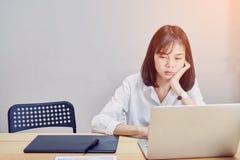 De bedrijfsvrouwen zitten lange tijd en spannen het computerscherm Omdat het werk is overbelast royalty-vrije stock afbeelding