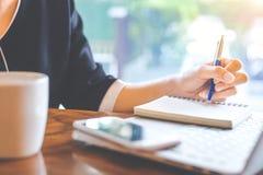 De bedrijfsvrouwenhand werkt bij een notitieboekjecomputer en takin royalty-vrije stock afbeelding
