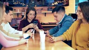 De bedrijfvrienden die smartphones in de koffie gebruiken stock videobeelden