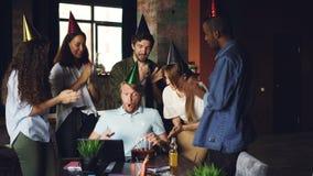 De bedrijfwerknemers wensen hun werkgever met verjaardags brengende cake geluk en de partijhoeden, jonge mens blaast kaarsen stock video