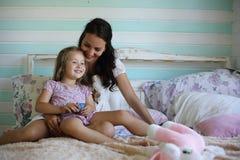 De bedtijd van de familielezing Vrij jonge moeder die een boek lezen aan dochter stock foto's