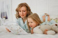 De bedtijd van de familielezing Vrij jonge moeder die een boek lezen aan haar dochter De moeder leest een sprookje aan haar docht royalty-vrije stock foto's