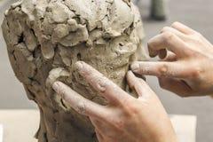 de beeldhouwer creeert een mislukking en zet zijn handenklei op het skelet van het beeldhouwwerk royalty-vrije stock afbeeldingen
