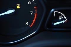 De beeldschermen op het autopaneel tonen aan dat de brandstof in de tank laag loopt royalty-vrije stock afbeeldingen