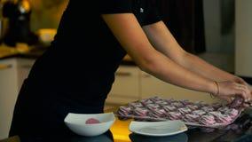 De begaafde banketbakker bestrooit heemst binnen in keuken stock videobeelden