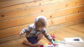 De begaafde jongen trekt een gele verf in kinderen` s centrum in hoofdklasse van art. Creatieve jong geitjejongen Het art. van de stock footage