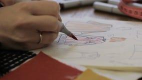 De begaafde klerenontwerper trekt kleren gebruikend viltpen, zittend bij lijst, trekt de kunstenaar modieuze beelden,  stock video