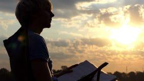 De begaafde Mens zit, leest en schrijft Zijn Nota's over een Riverbank bij Zonsondergang stock footage