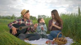 De begaafde vrolijke mens speelt snaarinstrument terwijl het wijfje met jong geitje zingt en terwijl in openlucht binnen ontspann stock video