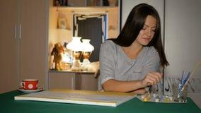 De beginkunstenaar schildert thuis haar eerste groot beeld op de lijst Het meisje neemt haar handen een schone borstel en kiest stock footage