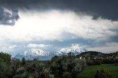 De behandelde berg van Colorado sneeuw, en een donkere donkere grijze hemel Stock Afbeeldingen
