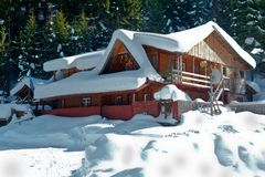 De behandelde sneeuw van de berg chalet stock fotografie