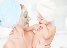 De behandeling van de familieschoonheid in de badkamers moeder en dochter het babymeisje maakt een masker voor gezichtshuid Stock Afbeeldingen