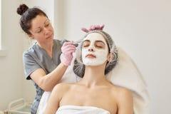 De behandeling van de kuuroordschoonheid, skincare concept De vrouw die gezichtszorg door schoonheidsspecialist krijgen bij kuuro royalty-vrije stock foto's