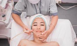 De behandeling van de meeëterzuiging op vrouwengezicht stock afbeeldingen