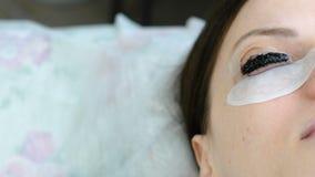 De behandeling van de schoonheid Close-upogen in vrouwen` s gezicht met verf op wimpers laminerende wimpers stock videobeelden