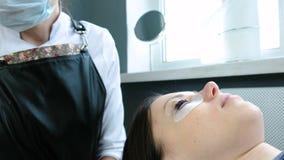 De behandeling van de schoonheid Cosmetologist zet zwarte verf op de zwepen laminerende wimpers stock video