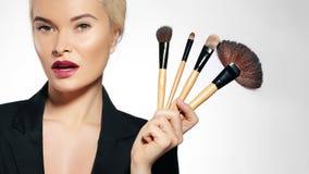 De behandeling van de schoonheid Meisje met make-upborstels De manier maakt Vrouw goed makeover Grimeur Applying Visage royalty-vrije stock foto's
