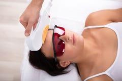 De Behandeling van schoonheidsspecialistgiving laser depilation aan Vrouwengezicht stock foto's