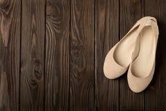 De beige ballerina's van vrouwen` s schoenen op houten achtergrond Stock Foto