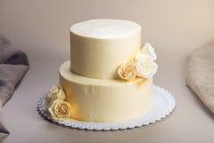 De beige die 2 tiered huwelijkscake met mastiekrozen wordt verfraaid bevindt zich op stoffenachtergrond Royalty-vrije Stock Foto