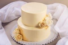 De beige die 2 tiered huwelijkscake met mastiekrozen wordt verfraaid bevindt zich op stoffenachtergrond Royalty-vrije Stock Afbeelding