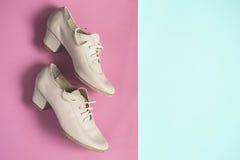 De beige vrouwelijke schoenen van de dansjazz op roze blauwe pastelkleurvlakte als achtergrond lagen Royalty-vrije Stock Foto's