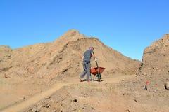 De bejaarde arbeider is gelukkig een kruiwagen met grond op wegcons. Stock Afbeeldingen