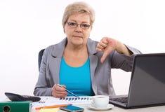 De bejaarde bedrijfsvrouw die duimen tonen verslaat en bij haar bureau in bureau, bedrijfsconcept werken Stock Foto