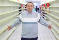 De bejaarde bevindt zich tussen lege planken in winkel Stock Foto