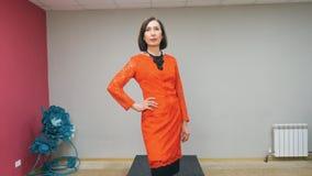 De bejaarde donkerbruine vrouw in rode kleding loopt het podium bij de lokale modeshow stock video