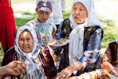 De bejaarde dorpsvrouw vertelt het verhaal van volkstradities en brandwondwierook in Kyrgyzstan royalty-vrije stock foto's