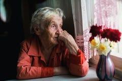 De bejaarde eenzame vrouw kijkt droevig uit het venster stock fotografie