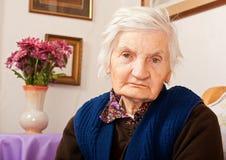 De bejaarde eenzame vrouw zit op het bed Stock Afbeelding