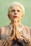 Portret van ernstige oude Kaukasische vrouwen biddende god Stock Afbeeldingen
