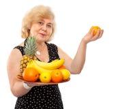 De bejaarde gelukkige vrouw behandelt verse vruchten royalty-vrije stock foto