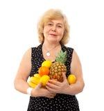 De bejaarde gelukkige vrouw behandelt verse vruchten stock foto's