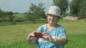 De bejaarde grootmoeder neemt foto's het park stock footage