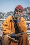De bejaarde Indische baardmens, hand op wang, kijkt voor, dragend culturele kabel en parels met wandelstok Stock Afbeelding